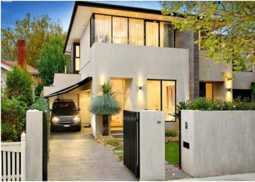 Eksterior rumah bernuansa tropis dengan taman dan pagar minimalis